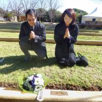 Yasuko Hayashi, a niece of Michiaki Wakaomi, who died of illness in 1945 as a prisoner of war in Australia, and her husband lay flowers at Wakaomi's grave in the Japanese War Cemetery in Cowra, New South Wales, in 2014. | KYODO
