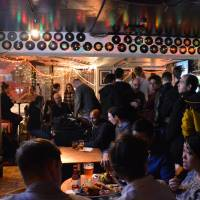 Patrons head to the bar at Good Heavens in Shimokitazawa before the first speaker starts at Tokyo Nerd Nite in January. | SHANNON SCHUBERT