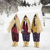 Women in traditional work pants stand in front of a shrine at the Inukko festival in Yuzawa in 2015. | JORDAN OXBOROUGH