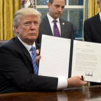 President Donald Trump signs an executive order formally pulling the U.S. out of the Trans-Pacific Partnership agreement in Washington on Jan. 23. | KYODO