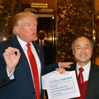 President-elect Donald Trump and SoftBank CEO Masayoshi Son speaks to members of the media in New York on Dec. 6. Son has pledged to invest $50 billion in the United States and create 50,000 jobs. | KYODO