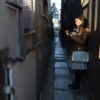 A woman checks her phone in one of the quaint alleyways of the area. | BENJAMIN PARKS