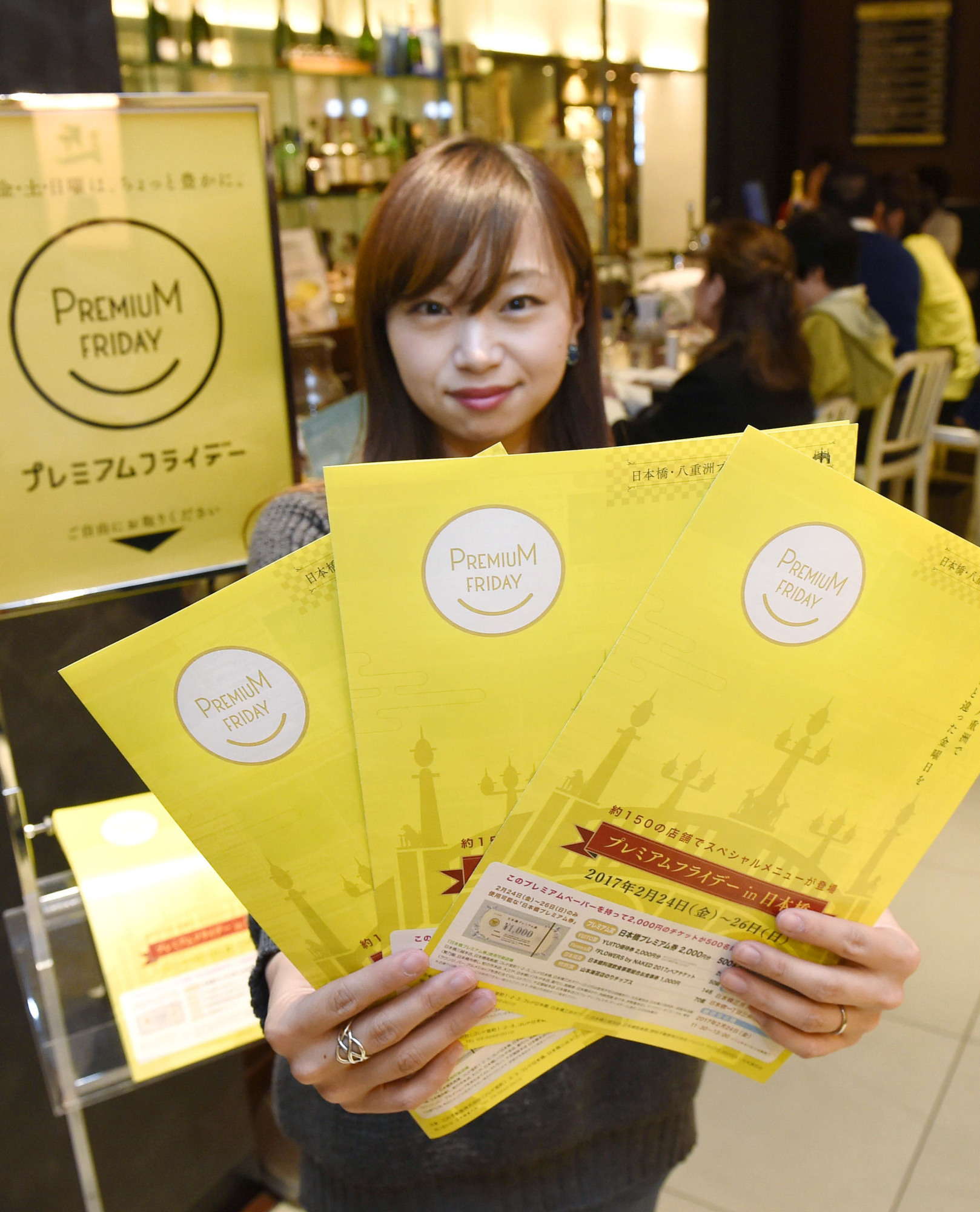 Friday night shopping: A woman holds up leaflets to promote a Premium Friday event at Daimaru Tokyo Store. | KYODO