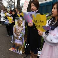 Protesters stand by a copy of a statue outside the Foreign Ministry in Tokyo last month symbolizing the 'comfort women' forced to provide sex for Japanese troops before and during World War II. | SATOKO KAWASAKI