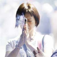 On a wing and a prayer: A woman prays at a Shinto shrine in Tokyo in May 2014. Professor Yoshinori Hiroi of Kyoto University's Kokoro Research Center notes that there are many more Shinto shrines in Japan than convenience stores.  ISTOCK   GETTY IMAGES