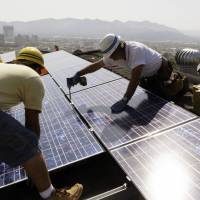 Catching some sun: Workers install solar electrical panels on the roof of a home in Glendale, California. | AP