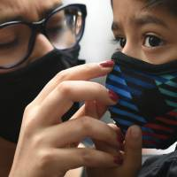 Clear air: A woman puts a protective mask on a young Indian protester at a rally in New Delhi in November.  afp-jiji | AFP-JIJI