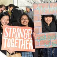 Wall of dissent: Americans and their supporters attend a march in Tokyo organized by the Alliance for an Inclusive America on Sunday 'to show support to those affected by the recent Muslim ban and other Trump administration actions impinging on the human rights of members of our shared global community.'   JOSH FRIES