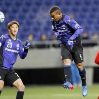 Gamba Osaka's Admilson scores on a first-half header against Malaysian club Johor Darul Ta'zim in an Asian Champions League playoff on Tuesday night at Suita Stadium. Gamba won 3-0. | KYODO