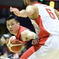 Japan's Yuki Togashi looks to pass the ball as Iran's Amirhossein Azari defends during the fourth quarter of Friday's exhibition game in Sapporo. Japan defeated Iran 85-74. | KYODO