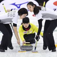 The Chubu Electric Power teams plays a shot at the national curling championships on Sunday. | KYODO