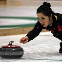 South Korea's Kim Kyeon-gae throws a stone in a women's curling round-robin match against Kazakhstan at the Asian Winter Games in Sapporo on Tuesday. South Korea won 18-1. | AP