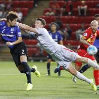 Gamba Osaka's Genta Miura heads the ball past Adelaide goalkeeper John Hall during their Asian Champions League match on Wednesday in Adelaide, Australia. | KYODO