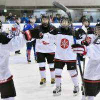 Japan players congratulate Shoko Ono (27) after she scored the third goal in Monday night's 3-0 win over South Korea in the women's hockey tournament at the Asian Winter Games in Sapporo. | KYODO