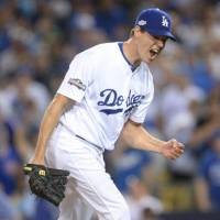 Journeyman hurler Rich Hill, seen celebrating on the mound during an NLCS game last season, has re-signed with the Los Angeles Dodgers for $48 million over three years. | USA TODAY / VIA REUTERS