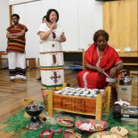 Haile Mahelet Alemayehu from the Ethiopian embassy in Tokyo prepares coffee in a coffee ceremony while Ethiopian Art Club of Japan representative Junko Yamamoto explains the procedure during a seminar at the Minato City Eco-Plaza on March 8. | MASAAKI KAMEDA