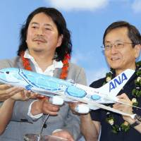 Chihiro Masuoka (left), who won a livery competition for A380 aircraft to be used on ANA's Honolulu routes, holds a model bearing his design with ANA President Osamu Shinobe at a news conference in Tokyo on Monday. | KYODO