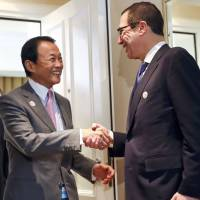 Finance Minister Taro Aso meets U.S. Treasury Secretary Steve Mnuchin for bilateral talks at the Group of 20 Finance Ministers and central bank governors meeting in Baden-Baden, Germany, on Friday. | REUTERS