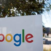 A man rides a bike past a Google sign and logo at the Googleplex in Menlo Park, California, last November. Google painted a bleak picture of cybersecurity trends Monday, saying the number of websites hacked rose 32 percent last year, with little relief in sight. | AFP-JIJI