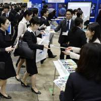 College students receive information handouts at a job fair held at Makuhari Messe in Chiba Prefecture on March 1. | KYODO