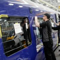 An employee fits a window on a Class 385 electric multiple unit (EMU) passenger railway carriage being built for use on the ScotRail franchise at Hitachi Rail Europe Ltd.'s railway train vehicle manufacturing facility in Newton Aycliffe, U.K. Hitachi Ltd. is aiming to expand its rail business in the U.S. by bidding for street and light rail projects as President Donald Trump urges the need to upgrade transportation across the country and spend as much as $1 trillion. | BLOOMBERG
