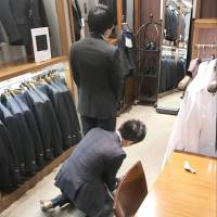 A participant in a suit-fitting event for sexual-minority students tries on a suit at the Marui store in Tokyo's Yurakucho district in February.   KYODO