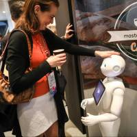 An attendee interacts with SoftBank Group Corp.'s Pepper humanoid robot on the second day of the Mobile World Congress in Barcelona, Spain, on Tuesday. | BLOOMBERG
