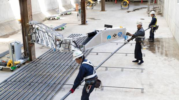 An arm-shaped robot developed by Shimizu Corp. helps construction workers lift 200-kg steel rods in Chiba Prefecture last August.