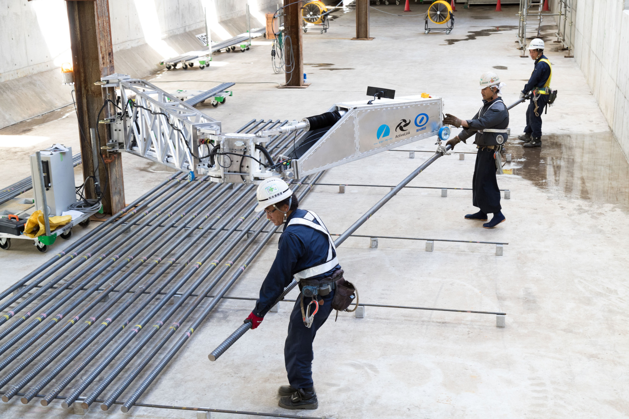 An arm-shaped robot developed by Shimizu Corp. helps construction workers lift 200-kg steel rods in Chiba Prefecture last August. | SHIMIZU CORP. / VIA KYODO