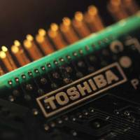 A Toshiba Corp. logo is seen on a printed circuit board. A state-backed consortium is reportedly mulling investing in Toshiba's memory chip business. | REUTERS
