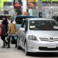 Visitors walk near a Toyota Motor Corp. Auris sedan displayed in the company's showroom in Tokyo on Feb. 8, 2011. The automaker is mulling future production of the new Auris in the U.K. | BLOOMBERG
