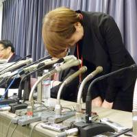 Chikako Yamada, president of travel agency Tellmeclub, apologizes during a news conference to announce its bankruptcy in Tokyo on Monday. | KYODO