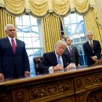 U.S. President Donald Trump signs an executive order alongside key advisers including National Trade Council chief Peter Navarro (third from right), in the Oval Office of the White House in Washington on Jan. 23. | AFP-JIJI