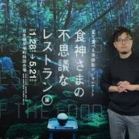 Restaurant recommendations: Tomohiko Suzuki stands in front of the poster for his exhibition, 'The Mysterious Restaurant of the Food God,' in Tokyo's Kayabacho area. | KYODO