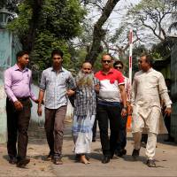 Security personnel bring Shaikh Mohammad Abul Kashem in front of media on Friday in Dhaka after his arrest on Thursday. | REUTERS
