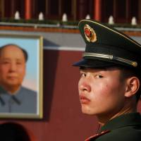 A paramilitary policeman looks back as he stands guard in Beijing's Tiananmen Square near a giant portrait of late Chinese Communist Party Chairman Mao Zedong on Friday. | REUTERS
