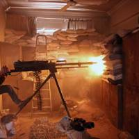 An opposition fighter from the Failaq al-Rahman brigade fires a heavy machine gun in Jobar, a rebel-held district on the eastern outskirts of Damascus, on Sunday. | AFP-JIJI