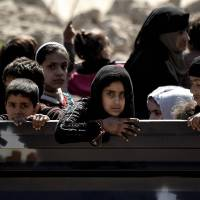Residents evacuate while advancing Iraqi forces battle Islamic State group fighters in western Mosul on Thursday. | AFP-JIJI