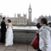 A couple prepare to pose for wedding pictures across from the Houses of Parliament on Thursday near Westminster Bridge (right) after it reopened to traffic following its closure during Wednesday's attack. | AFP-JIJI