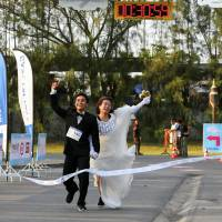 Sittichai Prasongsin, 27, and Sirada Thamwanna, 29, cross the finish line to win the 'Running of the Brides' race at a park in Bangkok on Saturday. | REUTERS