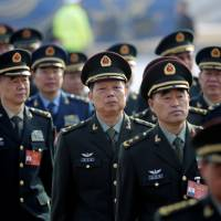 Military delegates from the People's Liberation Army head toward the Great Hall of the People in Beijing on Saturday to attend the annual session of the National People's Congress, China's parliament.   REUTERS