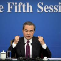 Chinese Foreign Minister Wang Yi gestures during a news conference on the sidelines of the National People's Congress in Beijing on Wednesday. | AP