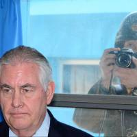 U.S. Secretary of State Rex Tillerson visits the demilitarized zone at the border village of Panmunjom, South Korea, as a North Korean soldier takes a photograph through a window on Friday. | REUTERS