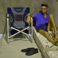 Ernie Woods, 82, sits in the safety of a temporary cyclone shelter in the town of Ayr in far north Queensland on Monday | AFP-JIJI