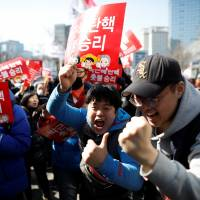 South Koreans celebrate outside the Constitutional Court in Seoul after the court removed President Park Geun-hye from office on Friday. | REUTERS