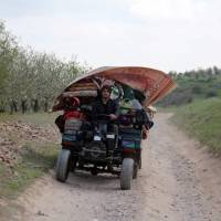 A Syrian man flees with his belongings from the village of Rahbet Khattab in the Hama province on Thursday. | AFP-JIJI