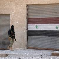 A rebel fighter walks past a roller shutter bearing the Syrian flag, in the village of Rahbet Khattab in the Hama province on Thursday. | AFP-JIJI