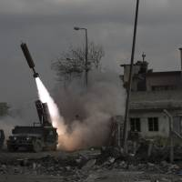 Federal Police Rapid Response Forces fire a rocket towards Islamic State positions near the old city, in Mosul, Iraq, Monday. | AP