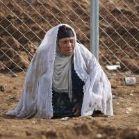 A displaced Iraqi woman from Mosul waits upon her arrival at the Hamam al-Alil camp on Monday during the government forces ongoing offensive to retake the western parts of the city from Islamic State (IS) group fighters. | AFP-JIJI