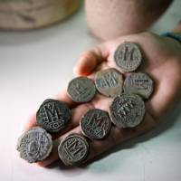 An archaeologist holds bronze coins from the Byzantine period during a media tour at Israel's National Treasures Storeroom, in Beit Shemesh, Israel, Sunday. | REUTERS